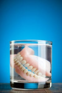 a pair of dentures in a glass of water
