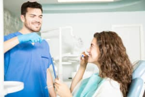 Dentist showing technique of brushing teeth to his female patient in dental clinic